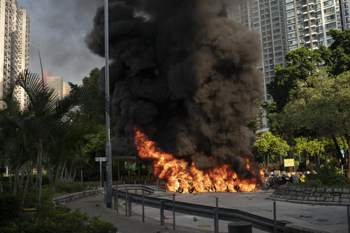 A row of motor-cycles go up in flames as anti-government protesters clash with police in Hong Kong, Oct. 1, 2019. (Photo: Felipe Dana/AP)