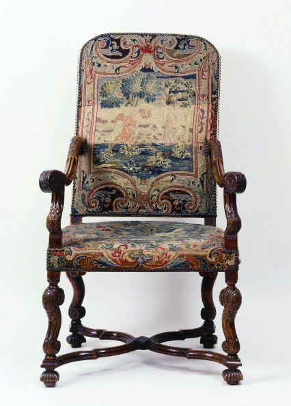 <p>The furniture from the reign of France's Louis XIV—the ruler who oversaw construction of Versailles—is characterized by intricate carving, rare wood, and heavy upholstery, like in this walnut seat with a dark, brocade fabric. Telltale signs of Louis XIV-style chairs include straight backs, curved arm rests, and crossed stretchers, which can either be H-or X-shaped (as on this chair). </p>