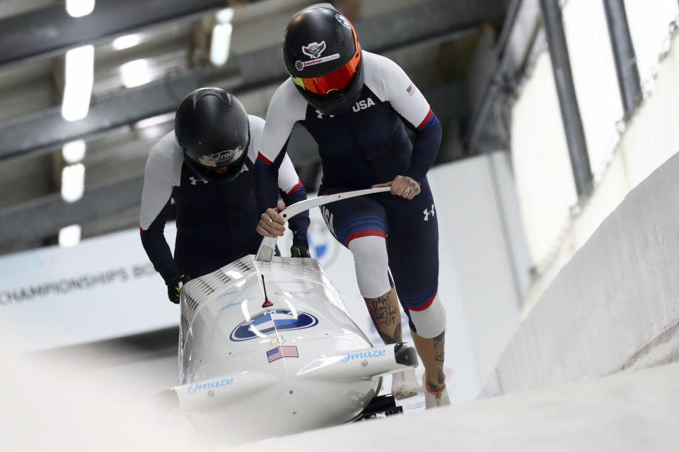 FILE - In this Feb. 5, 2021, file photo, Kaillie Humphries and Lolo Jones, of the United States, start during the two-women's bobsled race at the Bobsled and Skeleton World Championships in Altenberg, Germany. Reigning women's world bobsled champion and three-time Olympic medalist Humphries has asked the International Olympic Committee for a solution that would allow her to compete in this winter's Beijing Games even though her American citizenship will not be finalized. (AP Photo/Matthias Schrader, File)