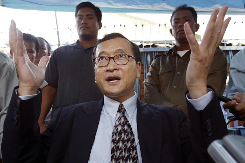 FILE - In this March 23, 2006 file photoay, , Cambodian opposition leader Sam Rainsy speaks to reporters outside the National Assembly building in Phnom Penh, Cambodia. Cambodian Prime Minister Hun Sen engineered a pardon for his most prominent rival Rainsy Friday, clearing the way for the self-exiled politician to return home and campaign in this month's general election. Rainsy has lived abroad since 2009 to avoid an 11-year prison term on charges widely seen as politically motivated. (AP Photo/Heng Sinith, File)