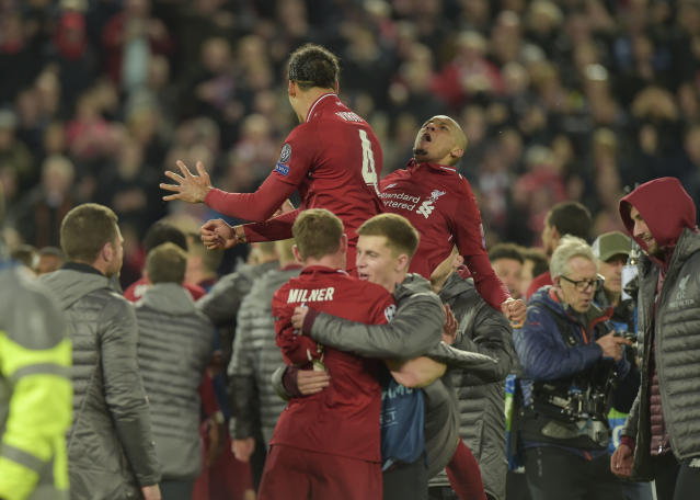 Virgil van Dijk and Fabinho are lifted up by fellow players