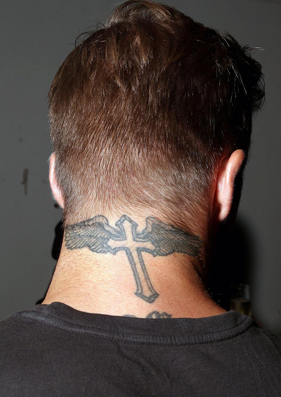 <p>A tattoo on the back of David's neck features a gothic-style cross and angel wings. The tattoo sits just about his 'Romeo' tattoo (not seen here) as a protective symbol watching over it. <br>[Photo: Rex] </p>