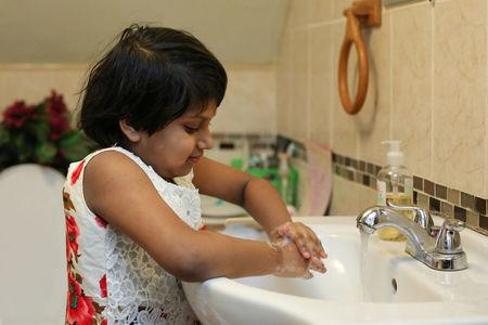 Nabiha A Chowdhury, 7, demonstrates her process for removing potential lead from her hands by washing them at her home in Buffalo, New York March 30, 2017.  REUTERS/Lindsay DeDario