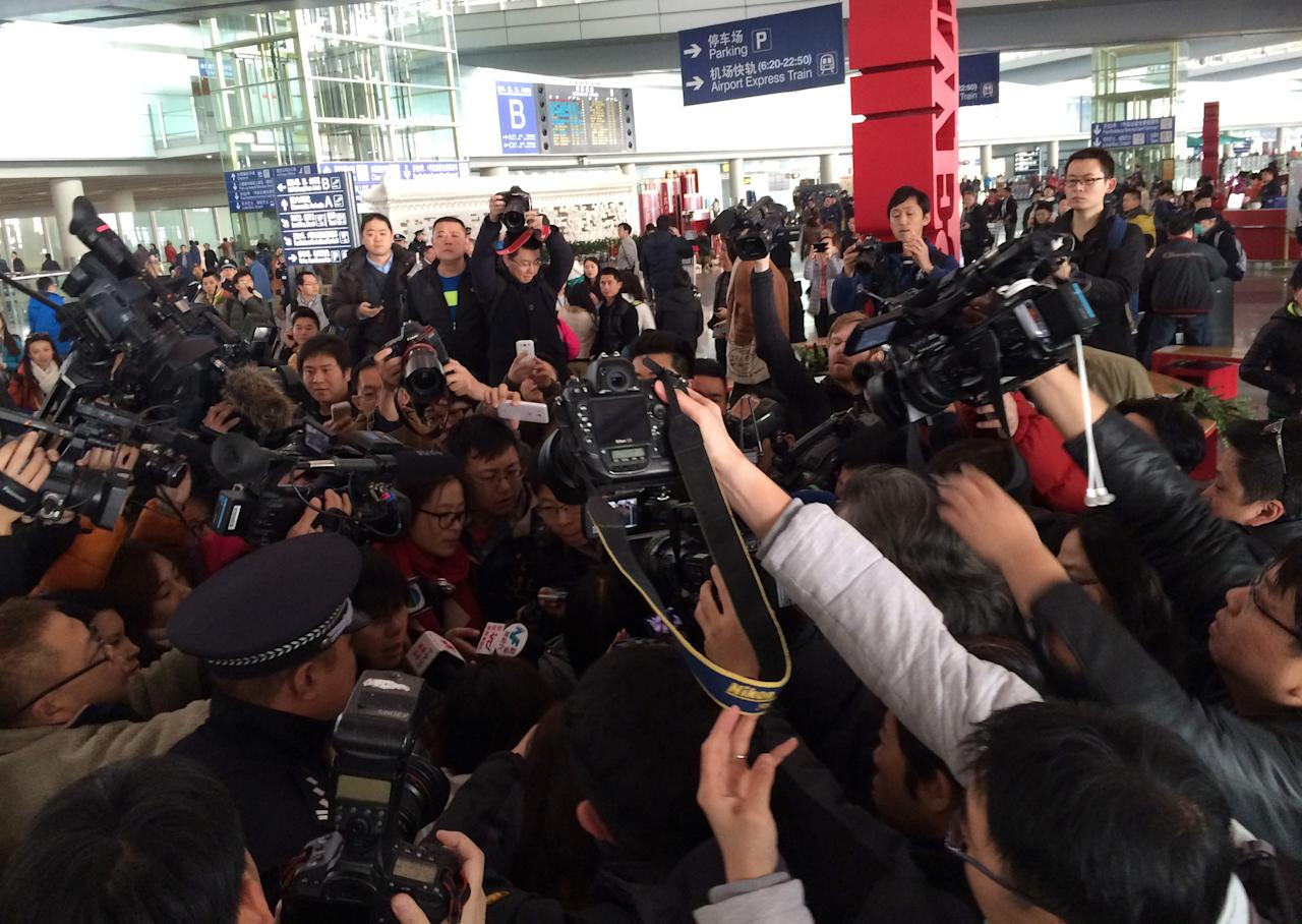 In this photo released by China's Xinhua News Agency, reporters crowd at Terminal 3 of Beijing Capital International Airport in Beijing, China Saturday, March 8, 2014 following a report that a Malaysia Airlines Boeing 777-200 lost contact on a flight from Kuala Lumpur to Beijing. (AP Photo/Xinhua, Luo Xiaoguang) NO SALES
