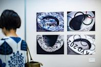 """A visitor walks in front of """"Toto Nolympics"""" by Shoko Miki during an anti-Olympics art exhibition in Tokyo"""