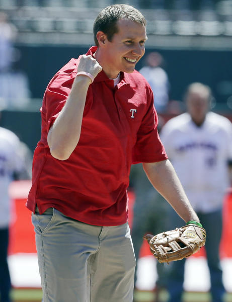 Robbie Parker pumps his first after throwing out the ceremonial first pitch before a baseball game between the Los Angeles Angels and Texas Rangers, Friday April 5, 2013, in Arlington, Texas. Parker, a North Texas native whose 6-year-old daughter, Emilie, was among the victims of the Sandy Hook school shooting in Connecticut, threw out the first pitch before the Rangers' home-opener, their favorite team. (AP Photo/Tony Gutierrez)