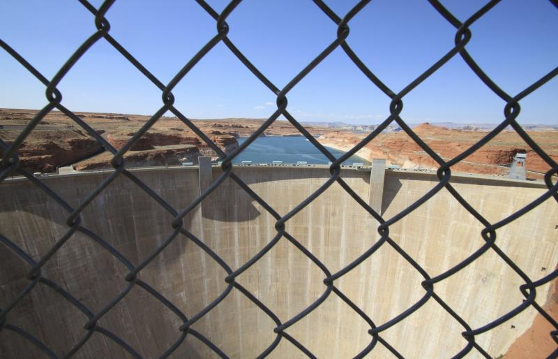 This Aug. 21, 2019 image shows Glen Canyon Dam beyond a chainlink fence in Page, Arizona. Environmental groups that have long pushed to bring down the dam along the Colorado River filed a lawsuit Tuesday, Oct. 2, 2019. They allege the U.S. Bureau of Reclamation ignored climate science when approving a 20-year operating plan for the dam. (AP Photo/Susan Montoya Bryan)