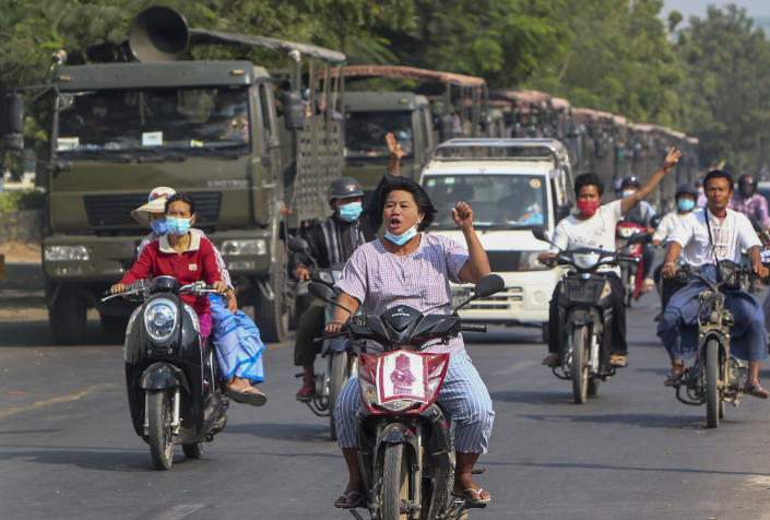 Demonstrators on motor bikes flash the three-fingered salute against the military coup as they ride pass military vehicles parked along a road in Mandalay, Myanmar on Wednesday, Feb. 17, 2021. The U.N. expert on human rights in Myanmar warned of the prospect for major violence as demonstrators gather again Wednesday to protest the military's seizure of power. (AP Photo)