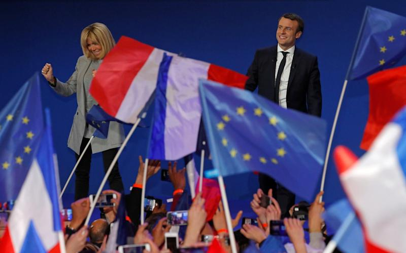 Emmanuel Macron arrives on stage with his wife Brigitte Trogneux to deliver a speech at the Parc des Expositions hall in Paris  - Credit:  PHILIPPE WOJAZER/REUTERS