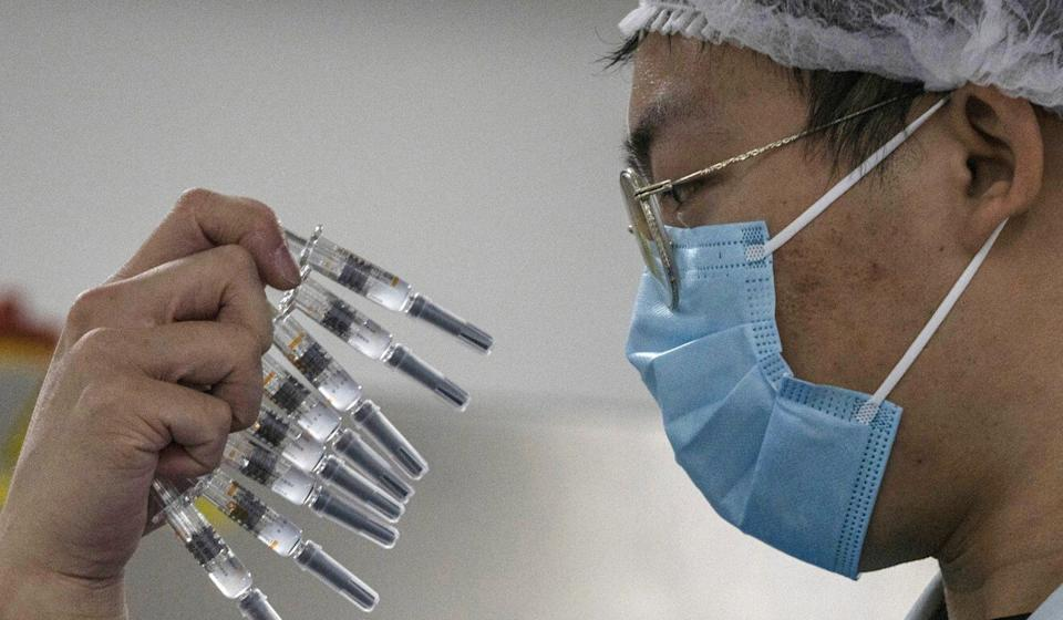 A worker inspects syringes of a vaccine for Covid-19 produced by Sinovac at its factory in Beijing. Photo: AP