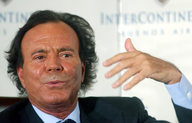 """FILE - In this April 12, 2004 file photo, Spanish singer Julio Iglesias gestures as he talks with reporters during a news conference to promote his new album """"Divorce"""" in Buenos Aires, Argentina. (AP Photo/Natacha Pisarenko, File)"""