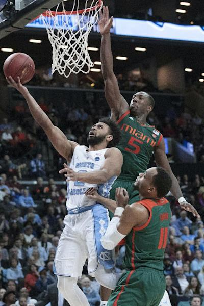 North Carolina guard Joel Berry II (2) goes to the basket against Miami guards Davon Reed (5) and Bruce Brown (11) during the second half of an NCAA college basketball game in the Atlantic Coast Conference tournament, Thursday, March 9, 2017, in New York. North Carolina won 78-53. (AP Photo/Mary Altaffer)