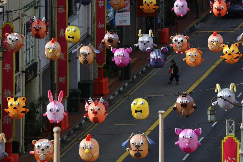 A pedestrian wearing a protective mask crosses a street decorated with Chinese zodiac lanterns at Chinatown on February 9, 2021 in Singapore.  (Photo by Suhaimi Abdullah/NurPhoto via Getty Images)