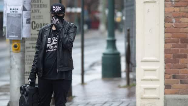 A man wears a mask and carries a wireless speaker playing music as he crosses Bank Street in Centretown on April 28. On Sunday, Ottawa health officials reported 174 new cases of COVID-19. (Andrew Lee/CBC - image credit)