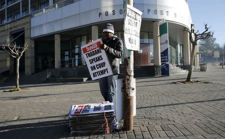 A worker hangs posters displaying newspaper headlines, in the capital Maseru
