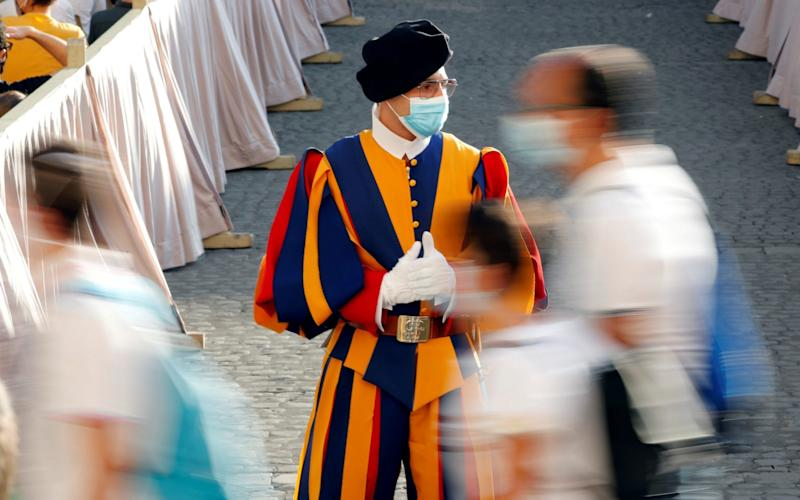 A Swiss Guard wearing a protective face mask patrols ahead of Pope Francis' weekly general audience at the San Damaso courtyard, at the Vatican, September 9 - REUTERS/Remo Casilli/File Photo