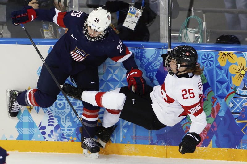 Kendall Coyne of the Untied States collides with Alina Muller of Switzerland against the boards during the first period of the 2014 Winter Olympics women's ice hockey game at Shayba Arena, Monday, Feb. 10, 2014, in Sochi, Russia. (AP Photo/Petr David Josek)
