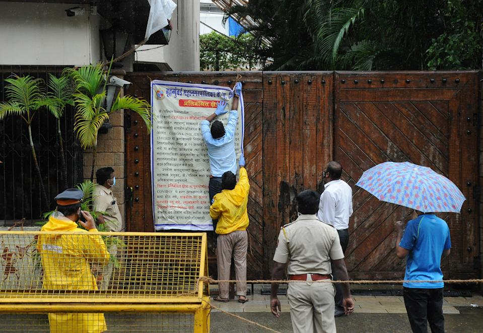Municipal workers put up a notice on Bollywood actor Amitabh Bachchan's bungalow gate. Bollywood actor Amitabh Bachchan tested positive for coronavirus and has been admitted to a hospital where he is being kept in quarantine. The actor requested those who had come in close proximity in the past ten days to get themselves tested for the virus. (Photo by Ashish Vaishnav/SOPA Images/LightRocket via Getty Images)
