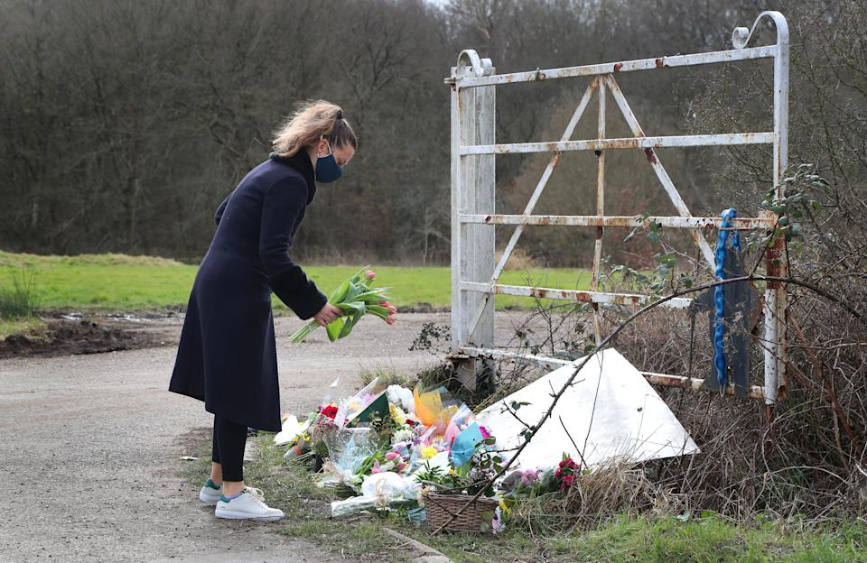 A lady lays flowers near the scene in Ashford, Kent, after a body found hidden in nearby woodland was identified as that of 33-year-old Sarah Everard. Serving police constable Wayne Couzens, 48, appeared in court on Saturday charged with kidnapping and murdering the 33-year-old marketing executive, who went missing while walking home from a friend's flat in south London on March 3. Picture date: Sunday March 14, 2021.