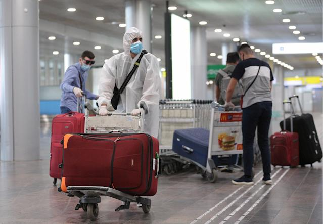 People who have arrived from New York City on an Aeroflot - Russian Airlines flight, carry their luggage at the arrivals area of Sheremetyevo International Airport. (Photo by Sergei Bobylev\TASS via Getty Images)