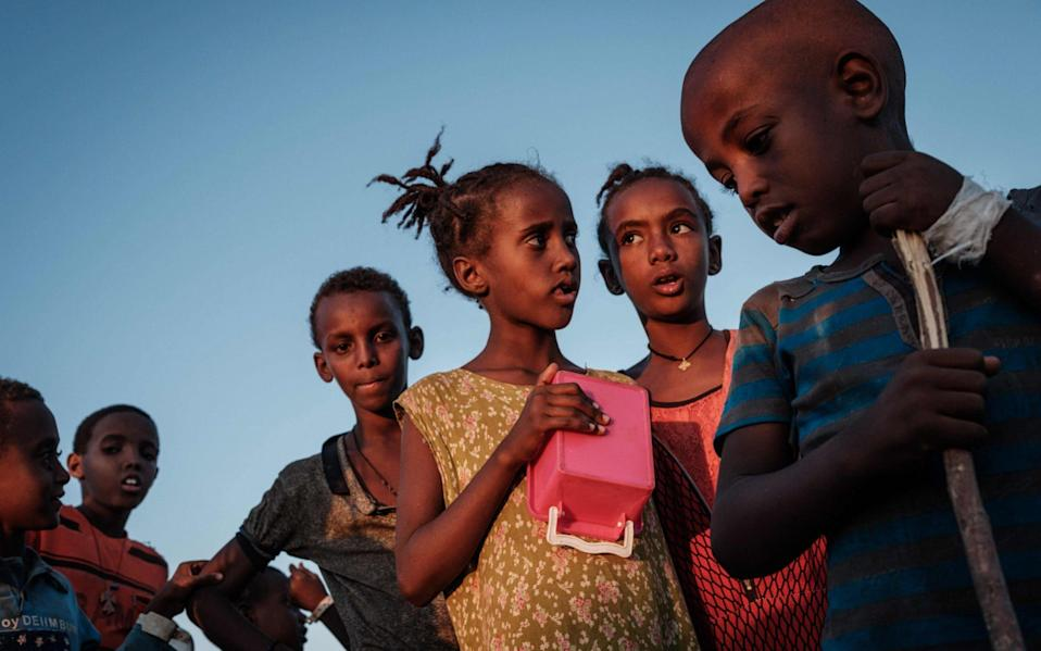 Ehiopian children, who fled the Ethiopia's Tigray conflict as refugees, wait for food distribution in the Um Raquba refugee camp - YASUYOSHI CHIBA /AFP