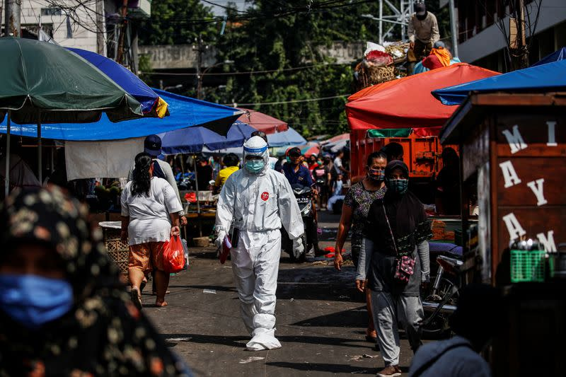 A healthcare worker wearing protective gear walks through a traditional market as swab samples are collected from vendors to be tested for the coronavirus disease (COVID-19), in Jakarta, Indonesia