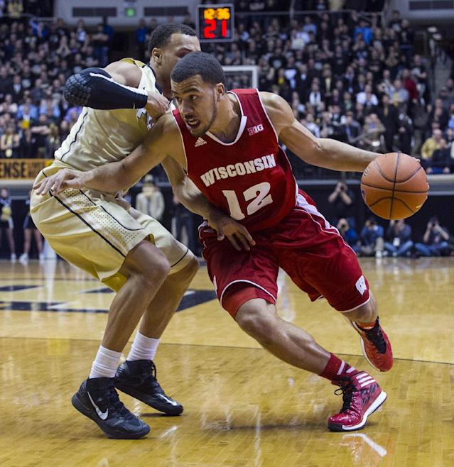 Wisconsin's Traevon Jackson (12) drives the ball past Purdue's Bryson Scott (12) in the first half of an NCAA college basketball game, Saturday, Jan. 25, 2014, in West Lafayette, Ind. (AP Photo/Doug McSchooler)