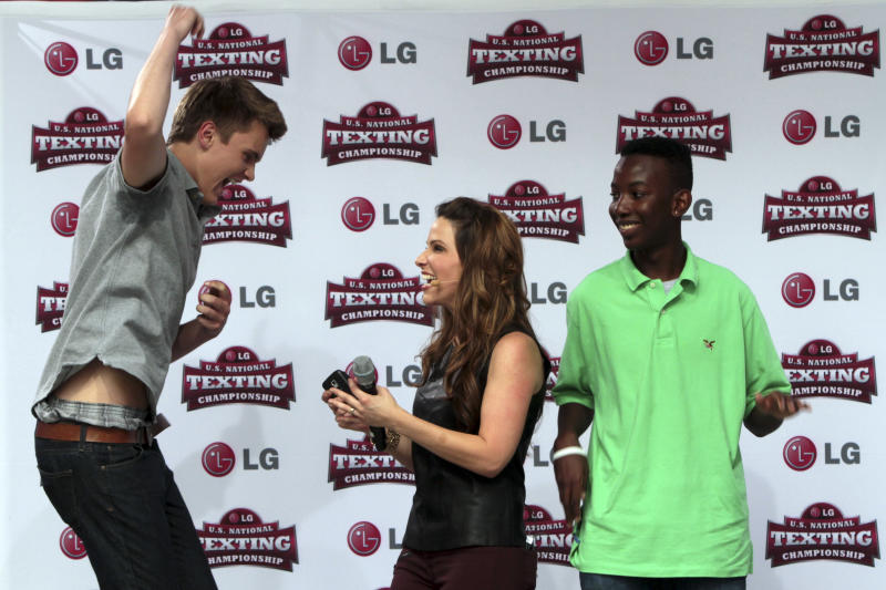 Austin Wierschke, left, of Rhinelander, Wis., reacts after winning the 2012 LG U.S. National Texting Championship as second place winner Kent Augustine, of Jamaica, N.Y. right, and host Stuart Brazell look on, Wednesday, Aug. 8, 2012 in New York. (AP Photo/Mary Altaffer)