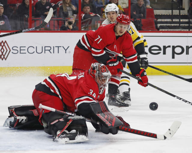 Carolina Hurricanes goaltender Petr Mrazek (34) eyes the puck as he deflects the shot of Pittsburgh Penguins' Sidney Crosby (87) defended by Carolina Hurricanes' Lucas Wallmark (71) during the second period of an NHL hockey game, Tuesday, March 19, 2019, in Raleigh, N.C. (AP Photo/Karl B DeBlaker)