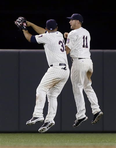 Minnesota Twins outfielders Clete Thomas, right, and Oswaldo Arcia celebrate the Twins 4-3 win over the Philadelphia Phillies in a baseball game, Wednesday, June 12, 2013 in Minneapolis. Thomas drove in the game-tying run in the eighth and scored the go-ahead run on a wild pitch by Phillies' Justin De Fratus. (AP Photo/Jim Mone)
