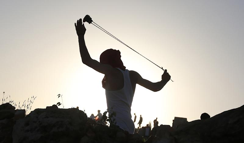 A Palestinian youth uses a sling shot to throw stones at members of the Israeli security forces during clashes in the West Bank village of Nabi Saleh on April 28, 2015