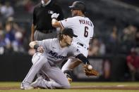 Miami Marlins third baseman Brian Anderson, left, reaches out for a late throw as Arizona Diamondbacks' David Peralta (6) arrives at third base with a triple during the seventh inning of a baseball game Monday, May 10, 2021, in Phoenix. (AP Photo/Ross D. Franklin)