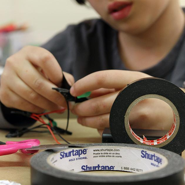 A young robot maker is learning how to create a complete electrical circuit.