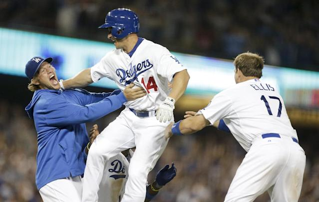 Los Angeles Dodgers' Mark Ellis, middle, celebrates with Clayton Kershaw, left, and A.J. Ellis after driving in the winning run against the New York Yankees during the ninth inning of a baseball game in Los Angeles, Tuesday, July 30, 2013. (AP Photo/Chris Carlson)