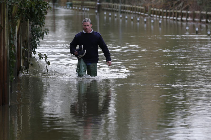 A man wades through a flooded road, in Shepperton, England, Tuesday, Feb. 11, 2014. The River Thames has burst its banks after reaching its highest level in years, flooding riverside towns upstream of London. Residents and British troops piled up sandbags to protect properties from the latest bout of flooding, but the river overwhelmed their defenses in several places Monday, leaving areas underwater. (AP Photo/Sang Tan)