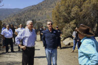 Nevada Gov. Steve Sisolak, front left, California Gov. Gavin Newsom, center, tour areas destroyed by wildfires near where the Tamarack Fire ignited earlier in July in Gardnerville, Nev., Wednesday, July 28, 2021. The governors of California and Nevada are calling for increased federal assistance as they tour an area blackened by one of several massive wildfires that have destroyed dozens of homes. Wednesday's tour of the Tamarack Fire along the state line comes as numerous wildfires char land and homes in a dozen states. (AP Photo/Sam Metz)