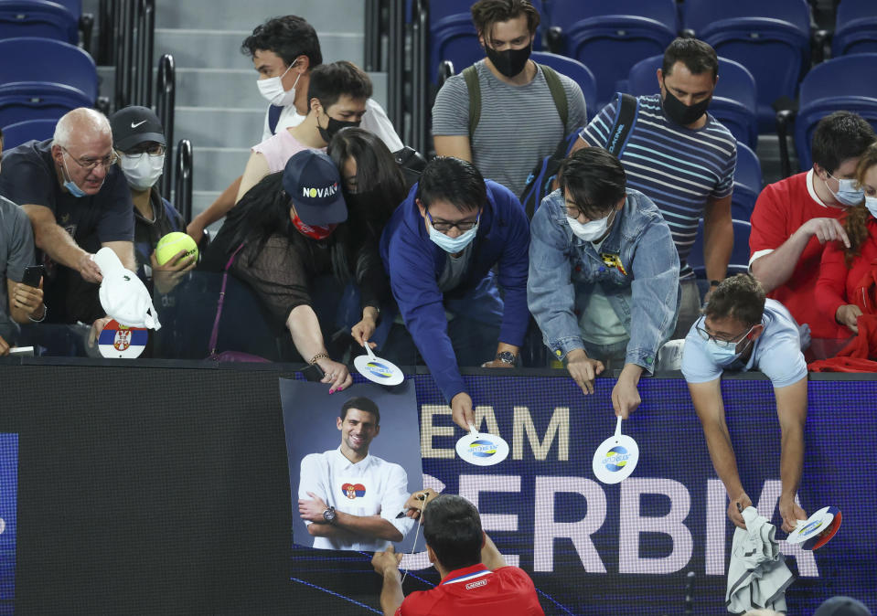 Serbia's Novak Djokovic signs autographs after defeating Germany's Alexander Zverev in their ATP Cup match in Melbourne, Australia, Friday, Feb. 5, 2021.(AP Photo/Hamish Blair)