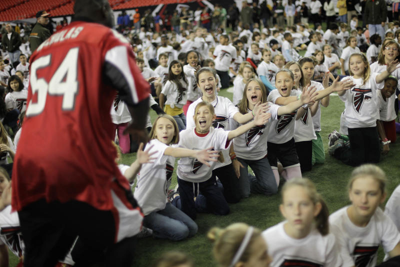 Atlanta Falcons linebacker Stephen Nicholas hi-fives students from Liberty Elementary school before an attempt to set the Guinness World Record for the largest virtual physical education class Tuesday, Dec. 7, 2010, in Atlanta. An adjudicator from the Guinness World Records verified that 2,288 elementary and middle students from across the metro area gathered at the Georgia Dome on Tuesday, setting the record for the largest virtual physical education class. (AP Photo/David Goldman)