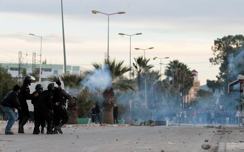 "Tunisian protesters clash with riot police, in Siliana, Tunisia, Saturday, Dec. 1, 2012. The army moved into a southwestern Tunisian town, an official and witnesses said Friday, the fourth day of protests that have injured more than 300 people. President Moncef Marzouki said on television that the North African country's government has not ""met the expectations of the people"" and asked that a new one, smaller and specialized to deal with the unrest, be formed. The current government has about 80 members. (AP Photo/Amine Landoulsi)"