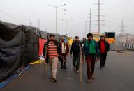 Farmers holding sticks patrol at the site of a protest against farm laws at Ghaziabad