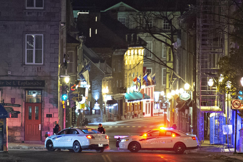 Police cars block the Saint-Louis Street near the Chateau Frontenac early Sunday, Nov. 1, 2020 in Quebec City, Canada. Police in Quebec City early Sunday arrested a man on suspicion of killing two people and injuring five others in a stabbing rampage near the provincial legislature on Halloween. (Jacques Boissinot/The Canadian Press via AP)