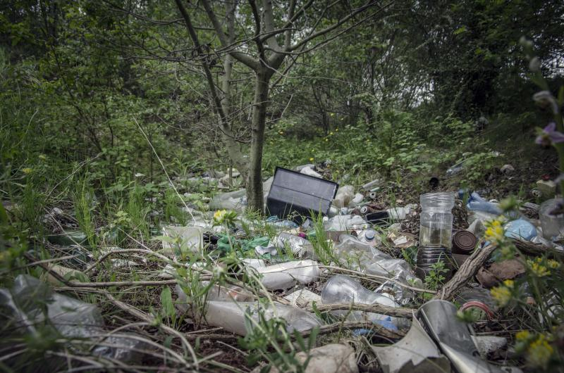 Piles of refuse, mainly plastic, abandoned amongst trees in urban woodland, West Midlands, UK.
