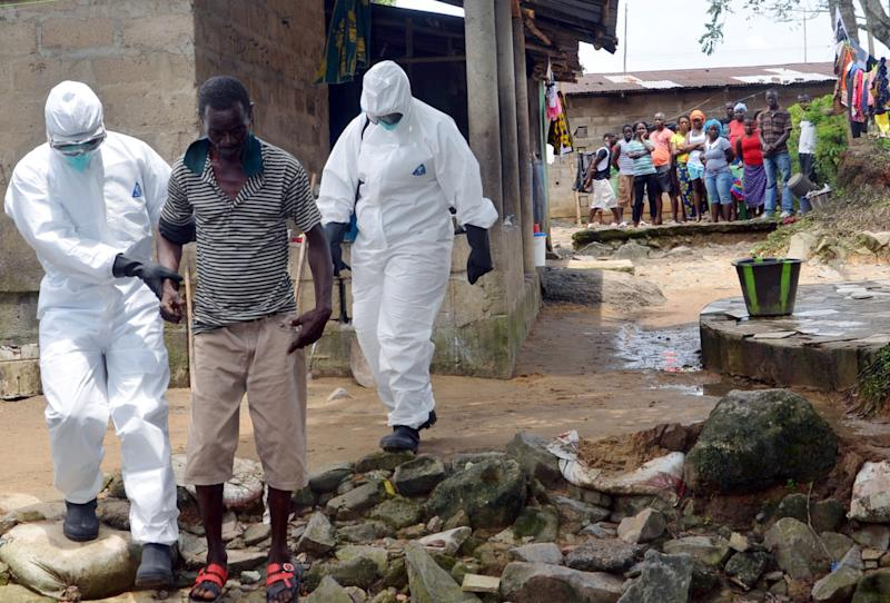 A picture taken on August 25, 2014 in Monrovia shows nurses wearing a protective suit escorting a man infected with the Ebola virus to a hospital