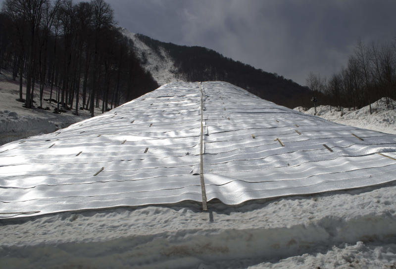 In this Friday, April 5, 2013 photo insulated blankets shimmer in the sun as workers are covering the snow pile in order to preserve it for the next winter outside Krasnaya Polyana, Russia. The Rosa Khutor Alpine skiing resort which is hosting the 2014 Winter Olympics is set to store nearly half a million cu. meters of snow collected in piles and tightly covered with insulated blankets.(AP Photo/ Nataliya Vasilyeva)
