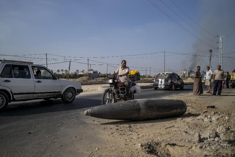 Palestinian motorists pause to inspect an Israeli shell laying unexploded in the central gaza town of Deir al-Balah, on August 1, 2014