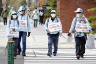 Staff walk around Odori Park with notes calling for refraining from watching a half-marathon to help curb the spread of the coronavirus in Sapporo, northern Japan, Wednesday, May 5, 2021. The half-marathon was held as a Tokyo 2020 test event three months before the Olympics open. (Hiroko Harima/Kyodo News via AP)
