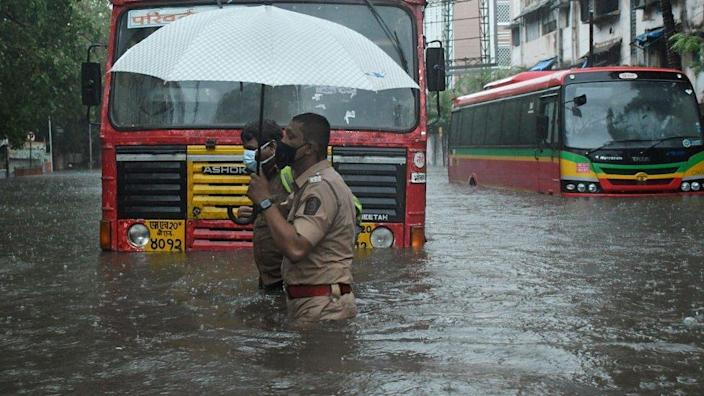 A policeman helps a public transport driver to cross a flooded street due to heavy rain caused by cyclone 'Tauktae' in Mumbai.