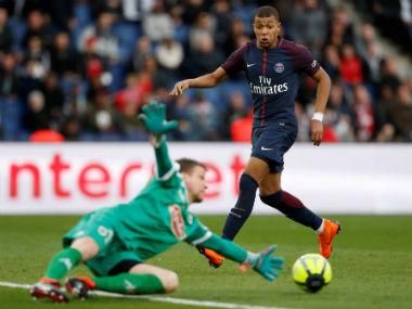 Angers' Ludovic Butelle makes a save as Paris Saint-Germain's Kylian Mbappe looks on. Reuters
