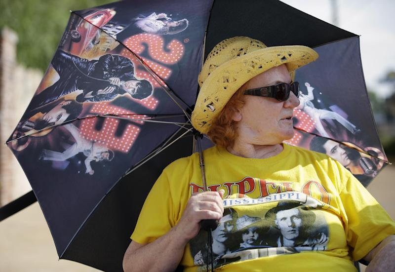Elvis Presley fan Ann Lawlor, of Croydon, England, waits in line outside Graceland, Presley's Memphis, Tenn. home, on Wednesday, Aug. 15, 2012. Fans are lined up to take part in the annual candlelight vigil marking the 35th anniversary of Presley's death. (AP Photo/Mark Humphrey)