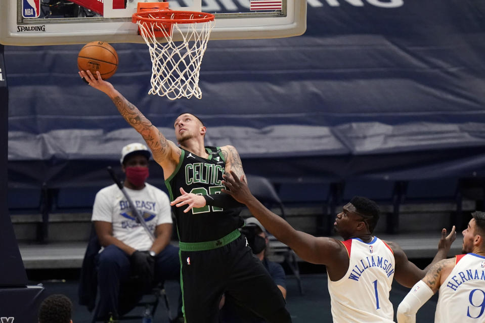Boston Celtics center Daniel Theis goes to the basket against New Orleans Pelicans forward Zion Williamson (1) in the first half of an NBA basketball game in New Orleans, Sunday, Feb. 21, 2021. (AP Photo/Gerald Herbert)